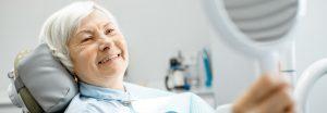Older lady showing off new dental implants.